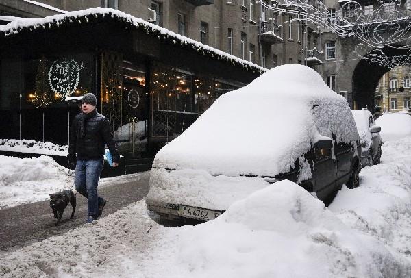 Un hombre pasa por cerca automóviles cubiertos de nieve en Kiev, Ucrania. (AP).
