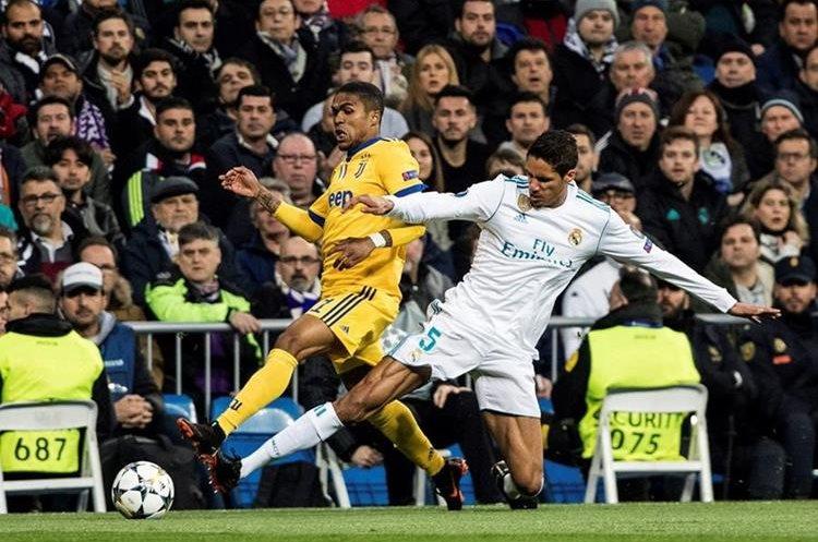 Varane pelea la pelota con Douglas Costa.