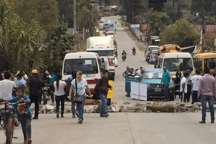 Un grupo de vecinos bloquea el paso en el kilómetro 199 de la ruta entre Santa Cruz Verapaz y San Cristóbal Verapaz. (Foto Prensa Libre: Eduardo Sam)