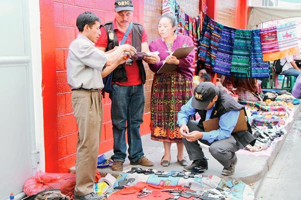 Investigadores de  la PNC y del MP verifican el registro de teléfonos móviles, en ventas informales y locales comerciales de Totonicapán. (Foto Prensa Libre: Édgar Domínguez)