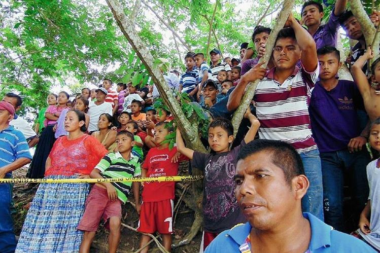 Curiosos observan el lugar donde fueron lanzados  los cadáveres de dos hombres en Sayaxché, Petén. (Foto Prensa Libre: Rigoberto Escobar)