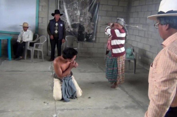 Sebastiana Gutiérrez Ixcoy azota a su hijo, Guillermo Alexander. (Foto Prensa Libre: Óscar Figueroa)