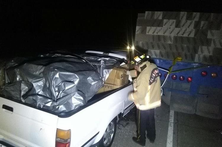 Un socorrista observa las cajas que iban en la palangana del picop donde viajaban las víctimas.  (Foto Prensa Libre: Ángel Julajuj)