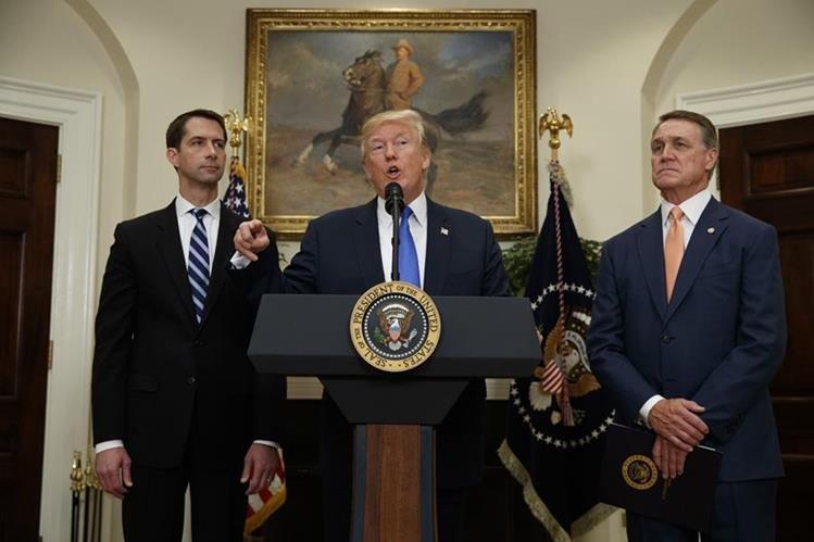Donald Trump, junto a los legisladores que proponen reducir en 50% la migración legal. (Foto Prensa Libre: AP)