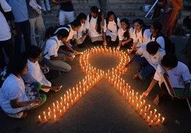 Estudiantes de la India encienden velas en memoria de las víctimas del cáncer en el mundo.(Foto Prensa Libre: AFP).