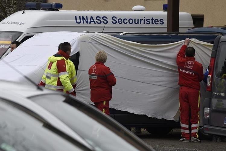 Forenses cubren el microbús involucrado en el accidente. (Foto Prensa Libre: AFP).