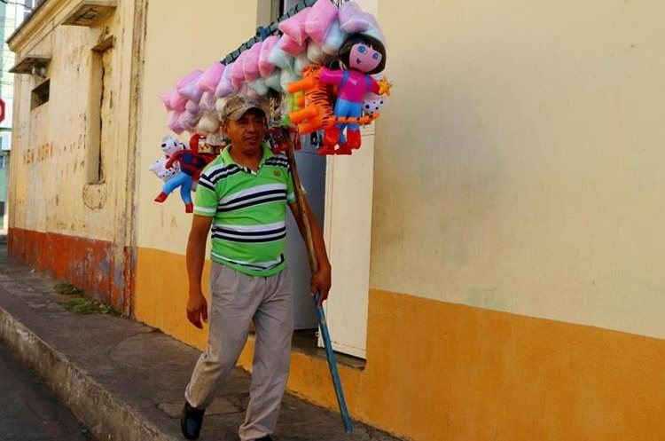 Tomás García recorre las calles y ofrece las bolsas de algodón de azúcar. (Foto Prensa Libre: Rolando Miranda)