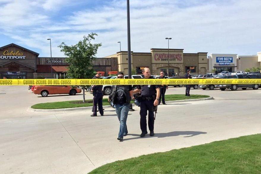 Un oficial de la policía de Waco (Texas), custodia a un arrestado el domingo tras el tiroteo entre pandillas rivales que dejó un saldo de más de 200 detenidos y 9 muertos.(Foto Prensa Libre: EFE).