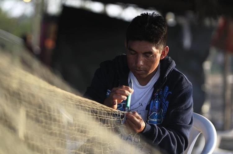 Un pescador repara la red que es la principal herramienta para su trabajo. (Foto Prensa Libre: Carlos Hernández)
