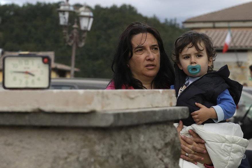 Un niño es abrazado por su madre en Amatrice, donde las autoridades temen que haya más víctimas menores de edad. (Foto Prensa Libre: AP).