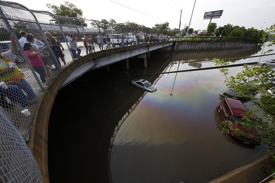 Curiosos observan en lo alto del puente los vehículos que fueron abandonados por los conductores para salvarse de morir. (Foto Prensa Libre: AFP).