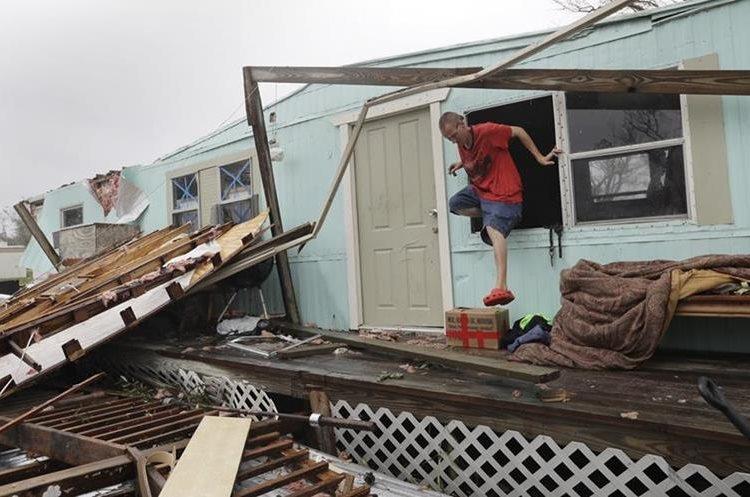 Sam Speights sale por la ventana de su cada después de ser destruida por el huracán Harvey.