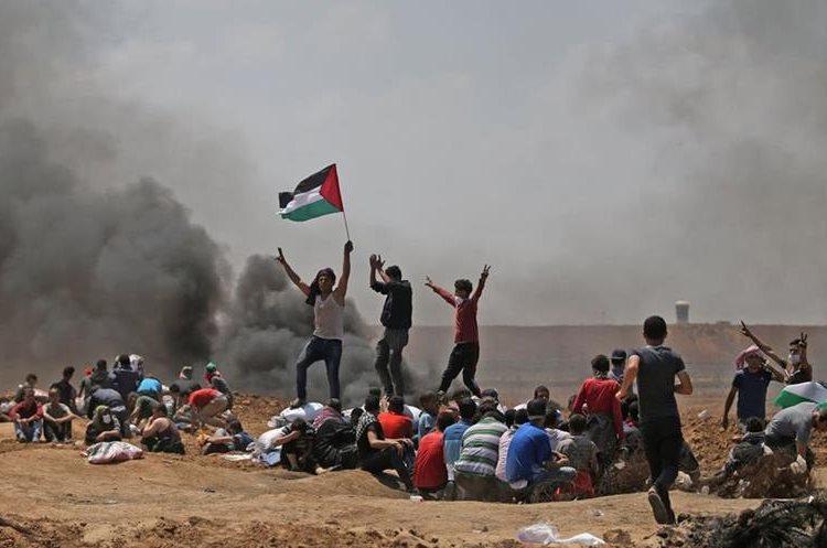 Manifestantes ondean una bandera palestina durante las protestas en la Franja de Gaza. (Foto Prensa Libre: AFP)