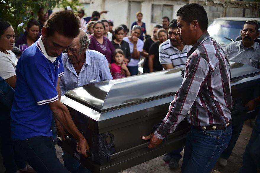 Parientes de una de las víctimas cargan el ataúd donde va su ser querido, quien falleció después que un camión lo arrollara junto con otras 27 personas en Mazapil. (Foto Prensa Libre: AFP).