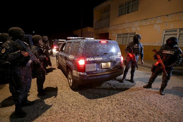 Policías vigilan el área del crimen donde murieron 10 personas entre ellas cinco policías. (Foto Prensa Libre: AFP).