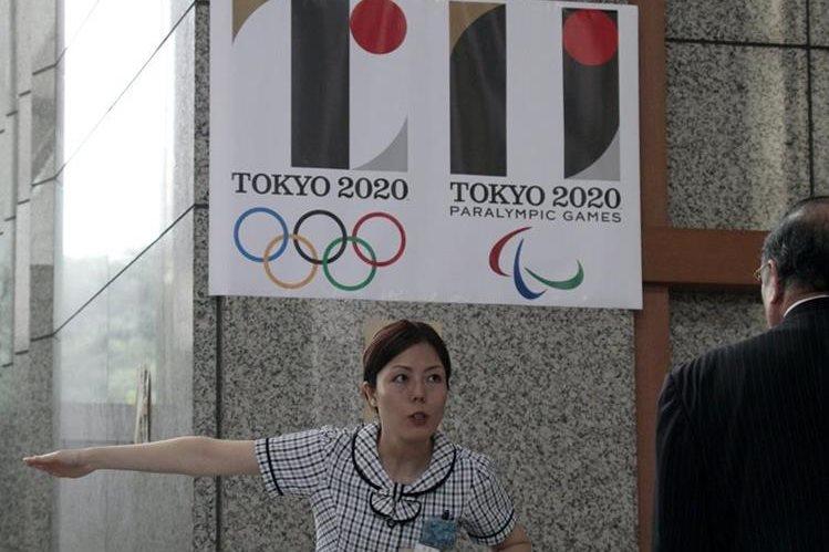 Una recepcionista da indicaciones a un visitante bajo el logo de los Juegos Olímpicos de Tokio 2020 en Tokio. (Foto Prensa Libre: EFE)