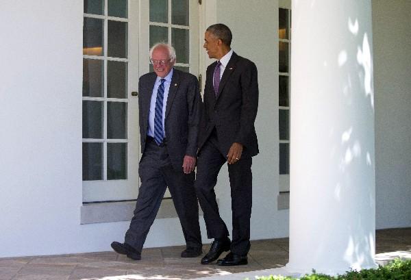 Barack Obama camina junto a Bernie Sanders en la Casa Blanca en Washington DC. (AP).