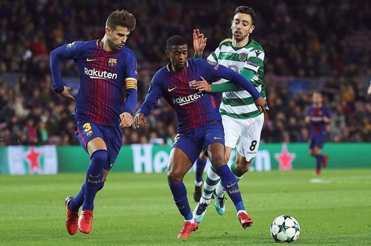 Los defensas del FC Barcelona, Gerard Piqué y Nelson Semedo, disputan el balón con Bruno Fernandes.
