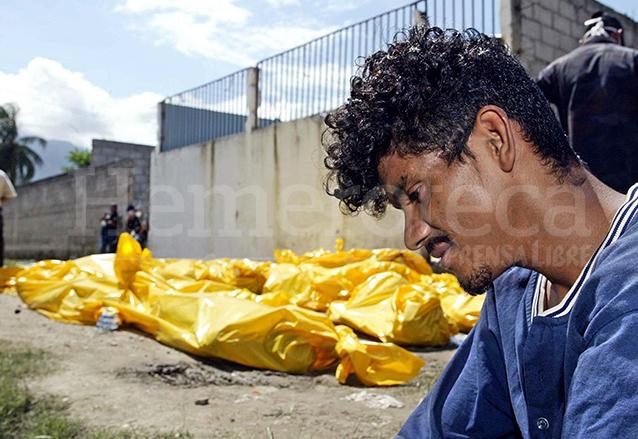 Un reo permanece junto a los cadáveres de sus compañeros fallecidos en un incendio en San Pedro Sula en 2004. (Foto: AFP)