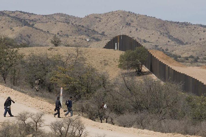 Los migrantes caminan hacia el muro fronterizo  en las afueras de Nogales, México. (AP).