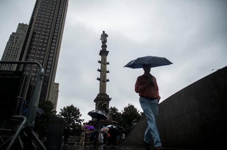 Varias personas camina cerca de la  la estatua de Cristóbal Colón en Nueva York mientras que un  grupo de personas pidela eliminación del monumento.