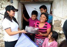 Andrea Cabrera de Ánfora entrega el pastel de chocolate a Iris Coyoy y su familia. (Foto Prensa Libre: Carlos Ventura)