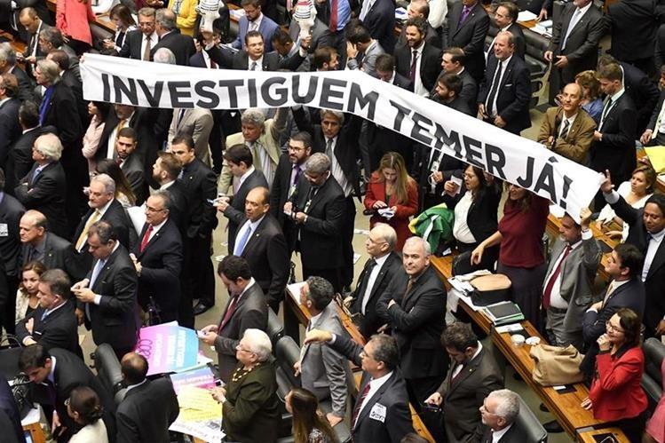 """Los legisladores de la oposición tienen una pancarta que dice """"¡Investiga a Temer ahora!"""".(Foto Prensa Libre:AFP)."""