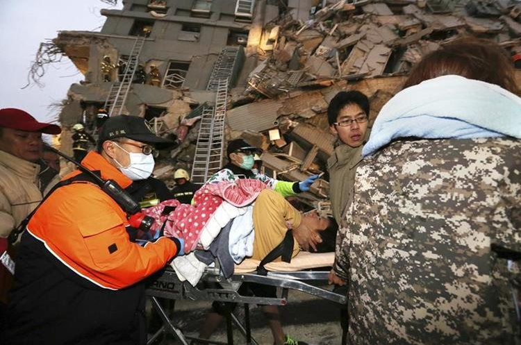 Rescue workers carry a man from the site of a toppled building after an earthquake in Tainan, Taiwan, Saturday, Feb. 6, 2016. The 6.4-magnitude earthquake struck southern Taiwan early Saturday, toppling at least one high-rise residential building and trapping people inside. Firefighters rushed to pull out survivors. (AP Photo) TAIWAN OUT