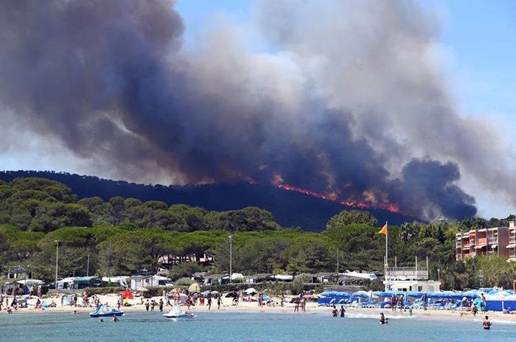 Turistas disfrutan de la playa mientras el fuego consume un bosque en Francia.