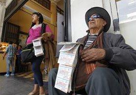 Francisco Gómez, de 90 años, vende números de lotería junto a su hija Marta Lidia Gómez. (Foto Prensa Libre: Paulo Raquec).
