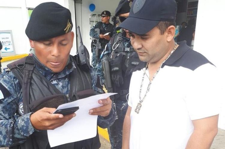 Agente antinarcóticos verifica la identidad del supuesto narco, Hugo Alejandro Chacón Cerna, el motivo de su detención. (Foto PNC)