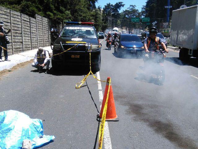 La PNC resguarda el lugar donde el cuerpo de un hombre fue lanzado desde un vehículo. (Foto Prensa Libre: Estuardo Paredes)