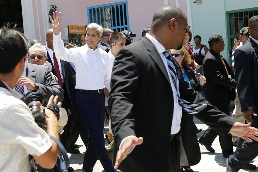 John Kerry devuelve el saludo a algunos cubanos que desde lejos le hicieron. (Foto Prensa Libre: AP).