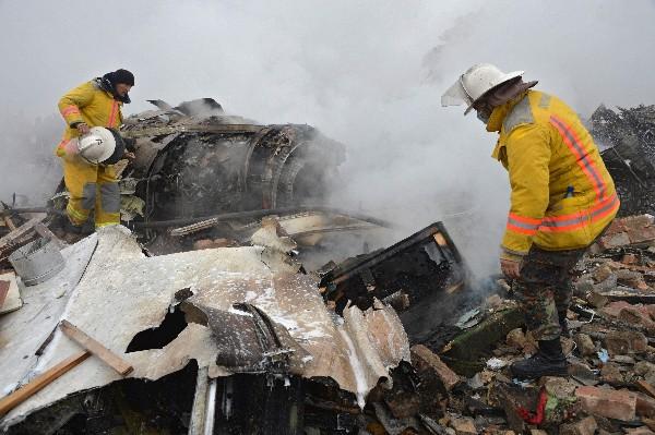 Rescatistas trabajan en la escena del accidente aéreo. (AFP).