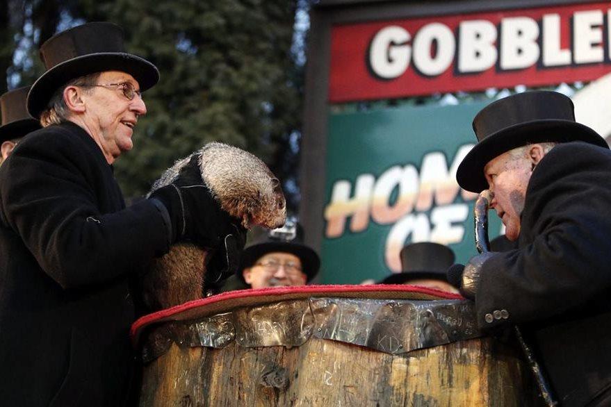 Ron Ploucha (i) sostiene a la marmota Phil, durante la celebración del Día de la Marmota. (EFE).