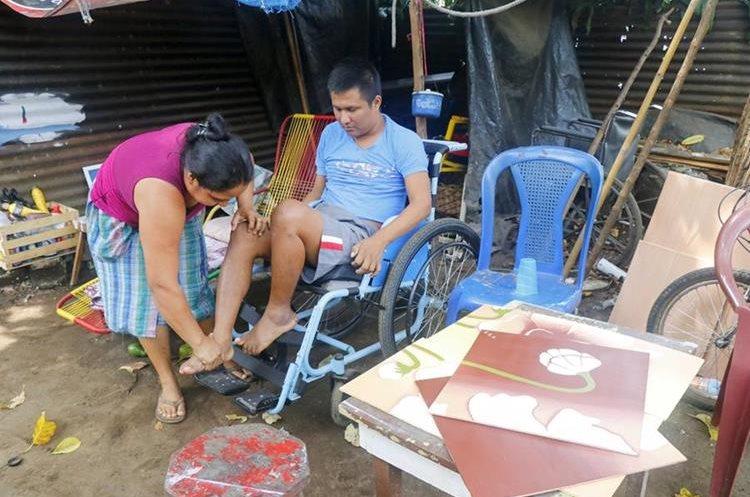 Ángela Esteban ayuda a su esposo a movilizarse en la silla de ruedas. (Foto Prensa Libre: Rolando Miranda)