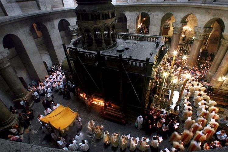 Varios religiosos rodean la estructura metálica que sostiene la tumba de Cristo.