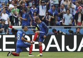 Dimitri Payet limpia los botines de Antoine Griezmann luego del segundo gol. (Foto Prensa Libre: AP)