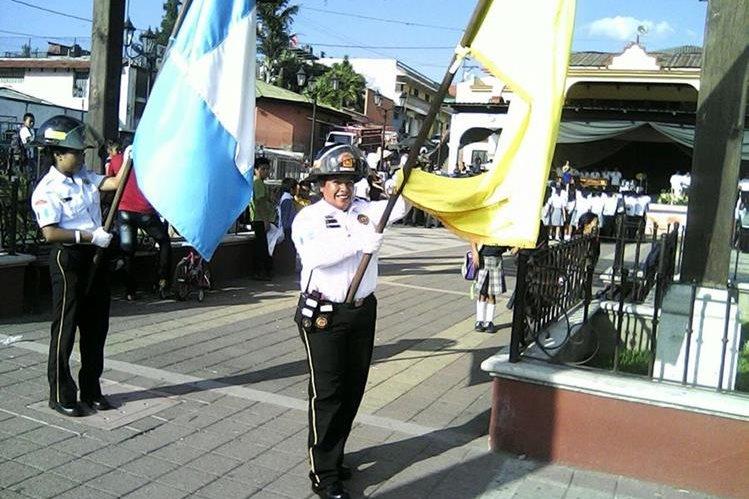 Miriam Luna porta la bandera de los Bomberos Voluntarios. (Foto Prensa Libre: Cortesía)