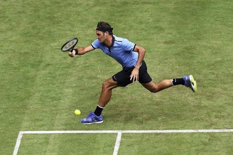 El tenista suizo Roger Federer devuelve la bola al japonés Yuichi Sugita durante su partido de primera ronda en el torneo de Halle, en Alemania.
