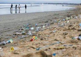 Varias personas caminan a la orilla del mar en Bali, Indonesia, en un área contaminada por desechos plásticos. (Foto Prensa Libre: EFE).