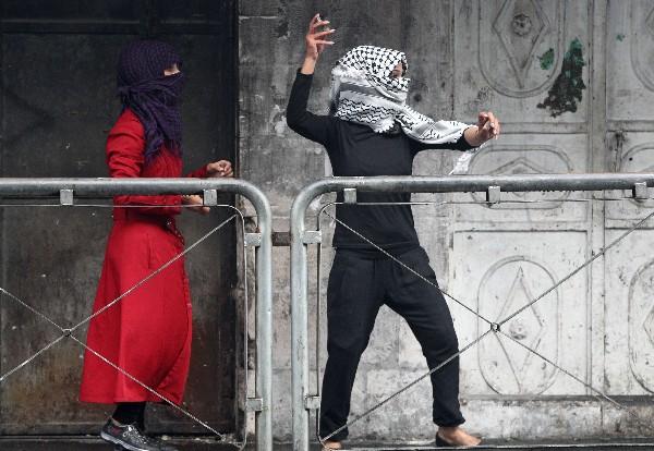 Mujeres palestinas lanza piedras a soldados israelíes.