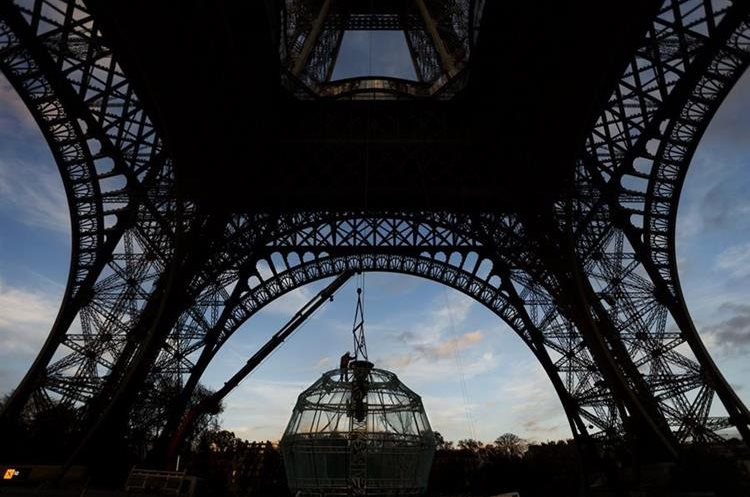 A worker helps with a structure to be installed as a Christmas decoration hanging from he Eiffel Tower, in Paris, Wednesday, Nov. 18, 2015. (AP Photo/Daniel Ochoa de Olza)
