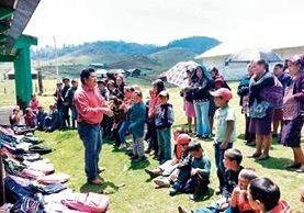 Daniel Mérida —de rojo— entrega donativo a niños de comunidades de Huehuetenango.