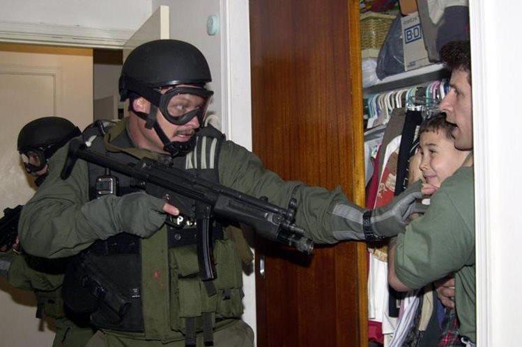 Momento en que un agente de inmigración de Estados Unidos encuentra a Elián González escondido en un armario. La foto causó polémica por la presunta brutalidad de la operación. (Foto: AP)