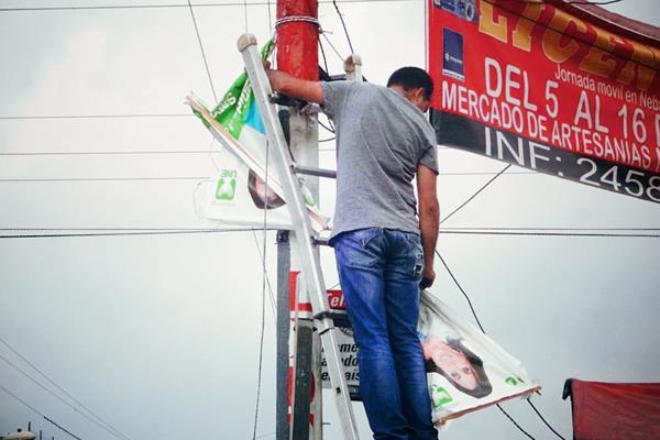 Un vecino  de Chicamán, Quiché, retira propaganda de partidos políticos de un poste. (Foto Prensa Libre: Óscar Figueroa)