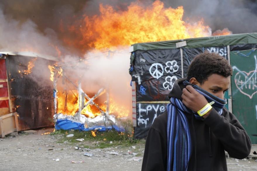 """Un migrante se protege el rostro al pasar junto a chabolas en llamas durante el desmantelamiento del campamento conocido como """"La Jungla"""" de Calais. (Foto Prensa Libre: EFE)."""