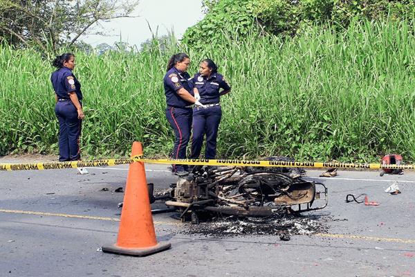 Socorristas observan los restos de la motocicleta en la que se conducía José Antonio Morataya Estrada, quien murió quemado luego de que fue arrollado por camión, en Masagua, Escuintla. (Foto Prensa Libre: Enrique Paredes)