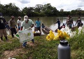 Pobladores retiran peces muertos en el río La Pasión. (Foto Prensa Libre: Conap)