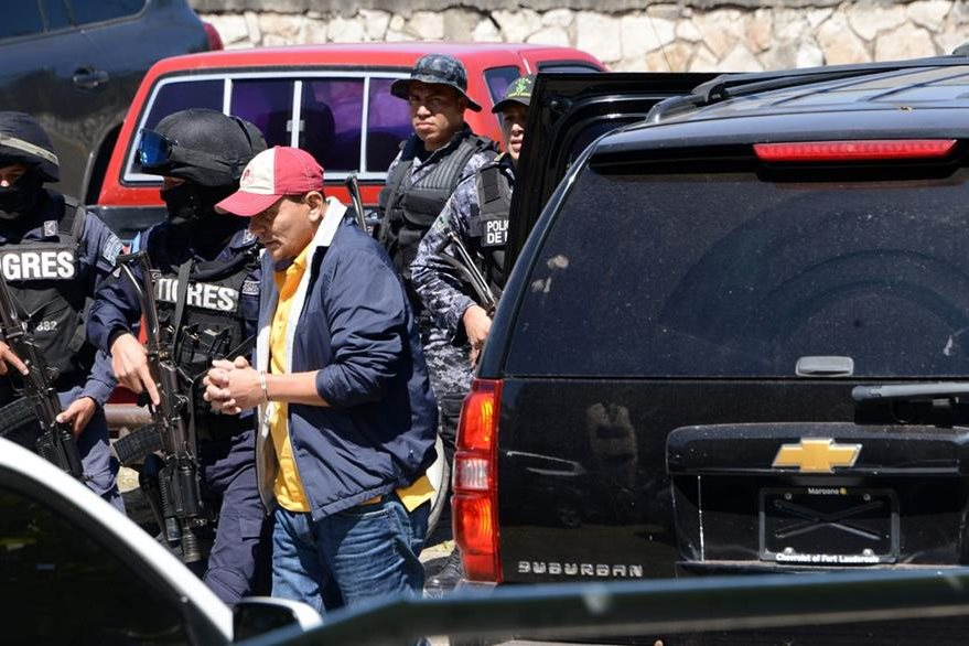 Agents of the Cobra Special Force and the Tigres squad escort Honduran alleged drug trafficker Jesus Soto Garcia as he is transported for a hearing in Tegucigalpa, on October 29, 2016.  Soto, who was requested in extradition by the United States, is allegedly related to Venezuelan presidential family members who were arrested on the same charges in New York. / AFP PHOTO / ORLANDO SIERRA
